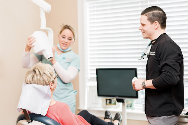 dentist smiling at righ with hygienist in background with x-ray machine and happy patient looking at them both