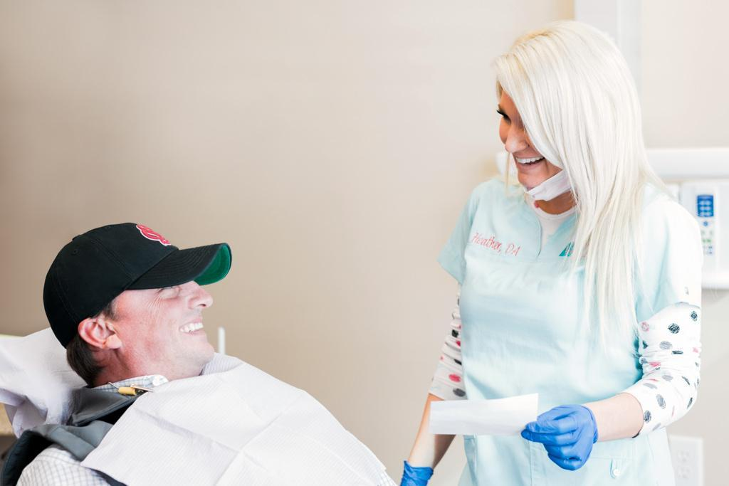 patient in hat looking up and laughing with laughing hygienist